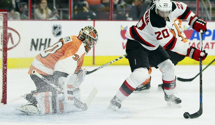 Philadelphia Flyers' Michal Neuvirth, left, defends as and New Jersey Devils' Lee Stempniak, right, looks to direct the puck in to the net in the first period of a preseason NHL hockey game Wednesday, Sept. 30, 2015, in Philadelphia. The Devils won 4-2. (AP Photo/Tom Mihalek)