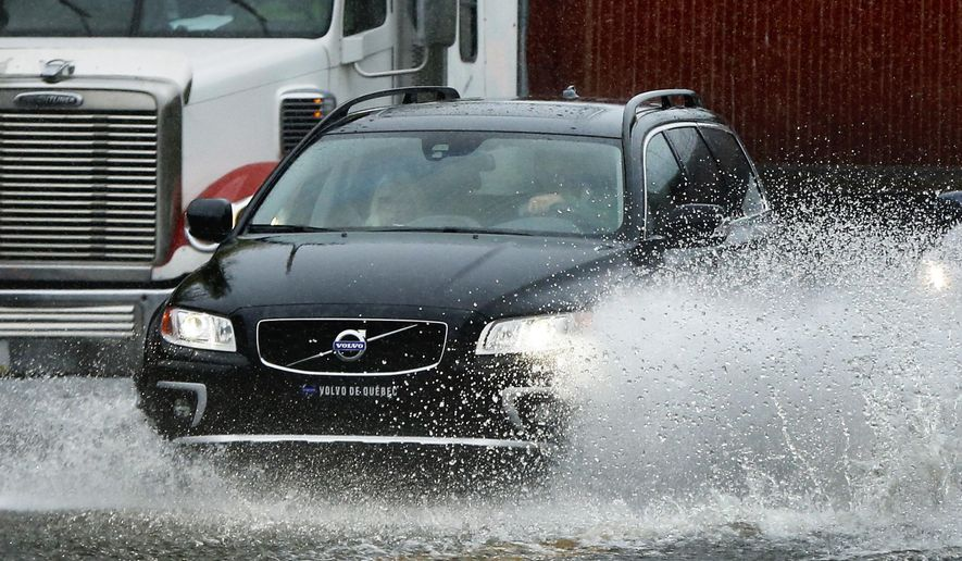 A motorist drives through flooding water in Portland, Maine, Wednesday, Sept. 30, 2015. Heavy rain has been moving through northern New England and a flood warning was issued for parts of Maine and New Hampshire. (AP Photo/Robert F. Bukaty)