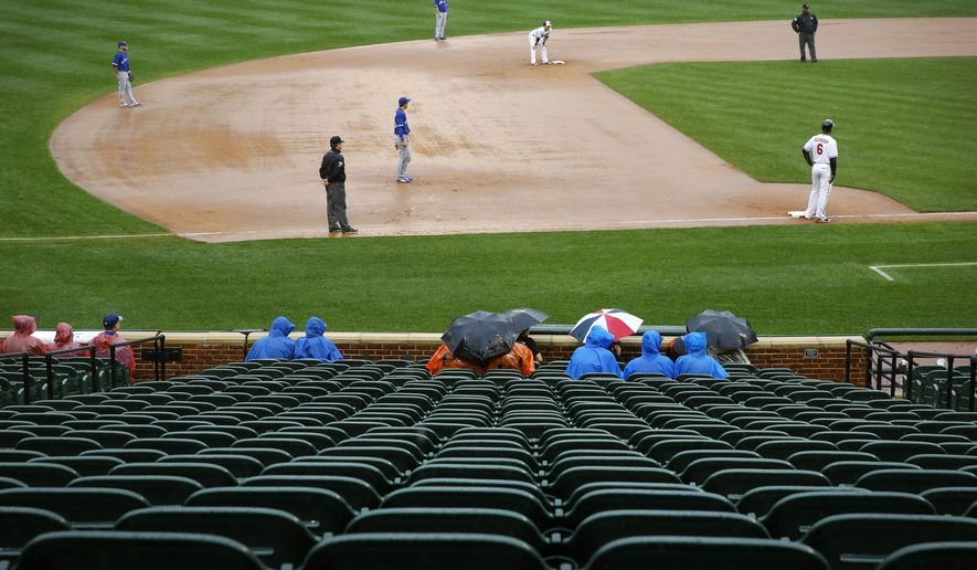 A handful of fans sit in the stands as rain falls during the first inning of a baseball game between the Baltimore Orioles and the Toronto Blue Jays, Thursday, Oct. 1, 2015, in Baltimore. (AP Photo/Patrick Semansky)
