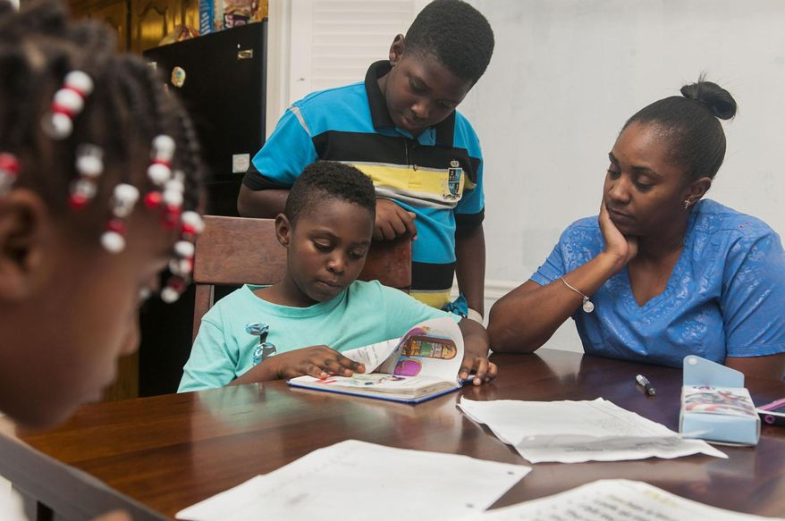 ADVANCE FOR MONDAY OCT. 5 - In this Sept. 23, 2015 photo, Ryan Jackson, left, practices his nightly reading homework with his brother Richard Jackson, center, and mother Raven White at their home in Wake Village, Texas. At 9 years old, Ryan Jackson has already experienced some of the most difficult moments life has to offer. When he was an infant, Ryan was diagnosed with sickle cell disease, a hereditary condition that leaves patients without enough healthy red blood cells to carry adequate oxygen throughout the body. (Jerry Habraken/The Texarkana Gazette via AP) MANDATORY CREDIT