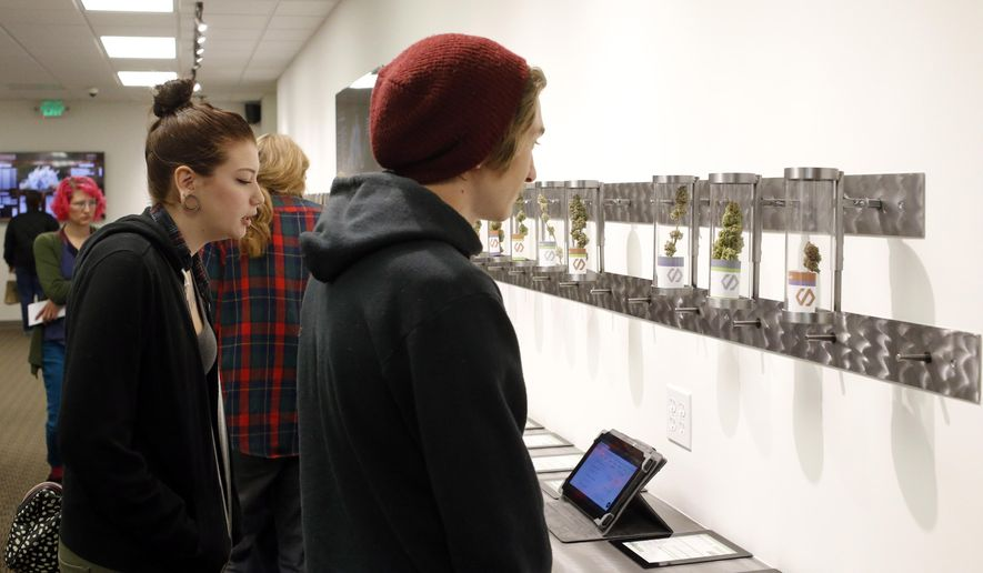 Customers look at product displays at Shango Premium Cannabis, in Portland, Ore., Thursday, Oct. 1, 2015. Oregon marijuana stores have begun sales to recreational users, marking a big day for the budding pot industry in the state. (AP Photo/Timothy J. Gonzalez)