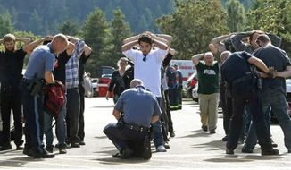 Police search students outside Umpqua Community College in Roseburg, Ore., Thursday, Oct. 1, 2015, following a deadly shooting at the college. (Mike Sullivan/Roseburg News-Review via AP)