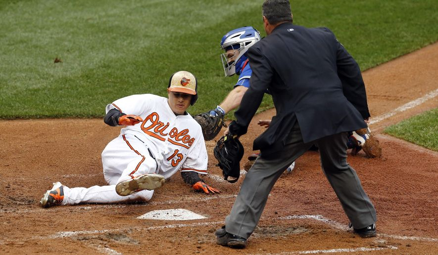 Baltimore Orioles' Manny Machado, left, slides past Toronto Blue Jays catcher Josh Thole and home plate umpire Rob Drake for a run on a single by Paul Janish in the second inning of a baseball game, Thursday, Oct. 1, 2015, in Baltimore. Baltimore won 6-4. (AP Photo/Patrick Semansky)