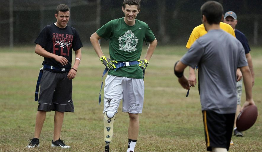 In this Tuesday, Sept. 29, 2015 photo high school student Matthew Freitas, of Weymouth, Mass., center, takes a break with teammates during a game of flag football, in Weymouth. This weekend, Freitas will join other athletes with physical and visual disabilities hoping to get noticed at a scouting event for the U.S. Paralympics. (AP Photo/Steven Senne)