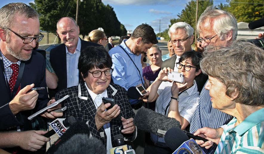 Death penalty opponent Sister Helen Prejean, center, tries to put death row inmate Richard Glossip on speaker phone outside the Oklahoma State Penitentiary, following a stay in his scheduled execution, in McAlester, Okla., Wednesday, Sept. 30, 2015. (AP Photo/Sue Ogrocki)