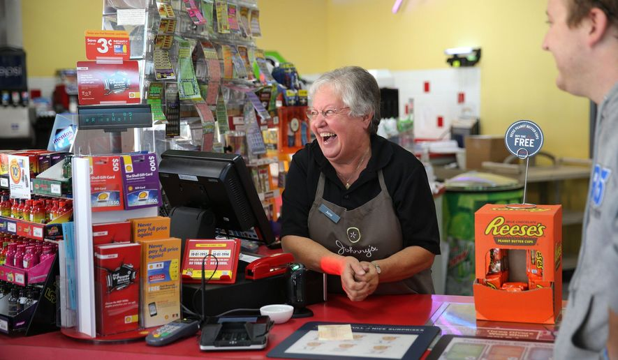 June Evans, cashier at the Three Rivers West Shell station in Three Rivers, Mich., laughs as customers arrive to talk about the store selling the winning $310.5 million lottery ticket, Thursday, Oct. 1, 2015. The station sold the only winning ticket in the drawing Wednesday night. (Mark Bugnaski/Kalamazoo Gazette-MLive Media Group via AP) ALL LOCAL TELEVISION OUT; LOCAL TELEVISION INTERNET OUT; MANDATORY CREDIT