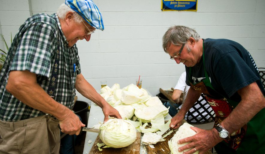 In this photo taken on Tuesday, Sept. 8, 2015, Bill Fournier and Walter Hagen, with the Great Lakes Bay Region DANK German Club, cut cabbage for sauerkraut at Stein Haus, in Bay City, Mich. The club is making the dish to serve at the DANK National Convention set for Oct. 2-4 in Bay City.  (Yfat Yossifor /The Bay City Times via AP) LOCAL TELEVISION OUT; LOCAL INTERNET OUT; MANDATORY CREDIT (