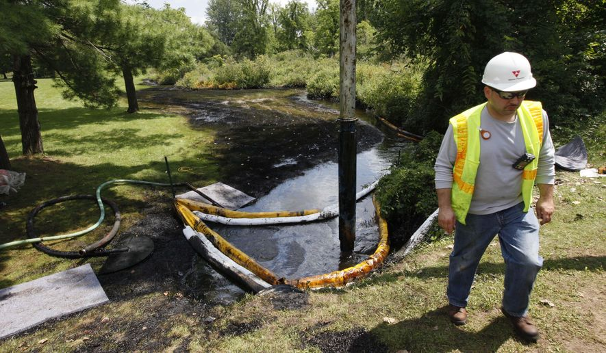 FILE - In this July 29, 2010 file photo, a worker monitors the water in Talmadge Creek in Marshall Township, Mich., near the Kalamazoo River as oil from a ruptured pipeline, owned by Enbridge Inc, is vacuumed out the water. The U.S. Department of Transportation wants to expand rules for pipelines carrying oil, gasoline and other hazardous liquids inspections requirements to include rural areas that are currently exempt, and for companies to more closely analyze the results of their inspections. (AP Photo/Paul Sancya, File)