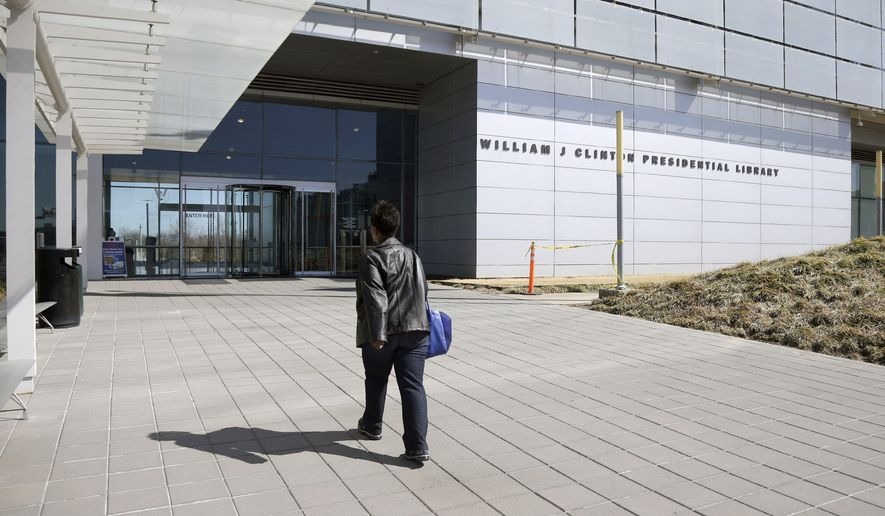 In this photo taken Thursday, March 13, 2014, a woman walks to the Clinton Presidential Library in Little Rock, Ark. The National Archives is scheduled to release thousands of pages of documents from Bill Clinton's administration Friday March 28, 2014. (AP Photo/Danny Johnston)