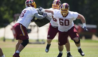 Washington Redskins rookie guard Spencer Long, right, tackle Tom Compton, center, and center Kory Lichtensteiger take part in drills during an NFL football practice at Redskins Park, on Wednesday, June 4, 2014, in Ashburn, Va. (AP Photo/ Evan Vucci)