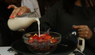 A customer pours organic full cream milk onto her cereal selection that includes chopped strawberries at the Cereal Killer Cafe in Brick Lane, London, Wednesday, Sept. 30, 2015. (AP Photo/Alastair Grant)