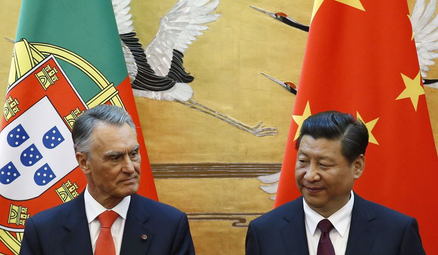 In this May 15, 2014, file photo, Portugal's President Anibal Cavaco Silva, left, and China's President Xi Jinping attend a signing ceremony at the Great Hall of the People in Beijing. When two Chinese companies appeared among the bidders to buy a troubled Portuguese bank this year, its staff took heart. They believed the potential buyers would do what Chinese investors are increasingly doing in Europe: save badly needed jobs and invest in expanding the business. (Kim Kyung-hoon/Pool Photo via AP)