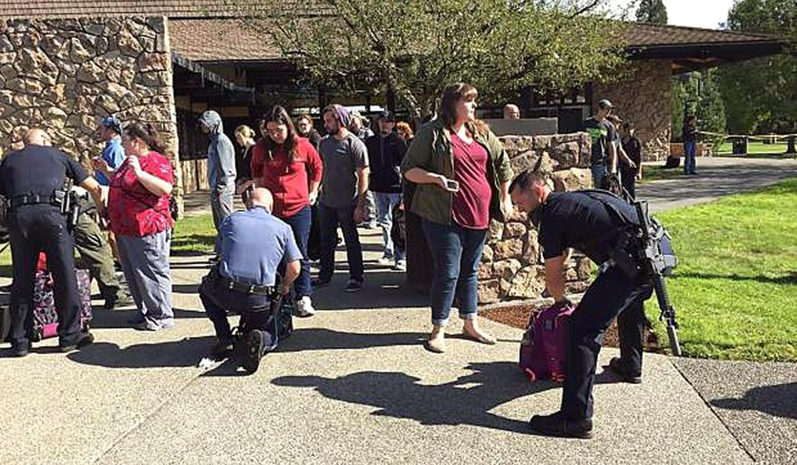 Police search students outside Umpqua Community College in Roseburg, Ore., Thursday, Oct. 1, 2015, following a deadly shooting at the southwestern Oregon community college. (Mike Sullivan/Roseburg News-Review via AP)