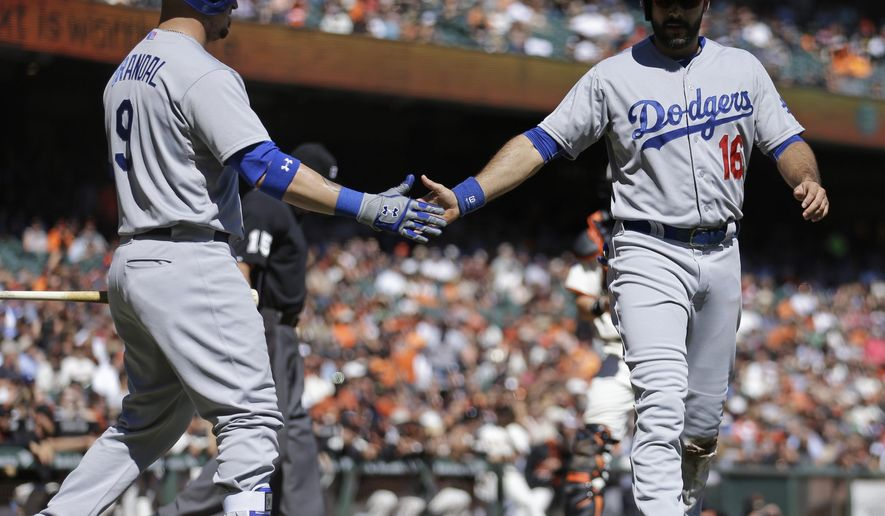 Los Angeles Dodgers' Andre Ethier, right, is congratulated by Yasmani Grandal (9) after scoring against the San Francisco Giants in the second inning of a baseball game Thursday, Oct. 1, 2015, in San Francisco. Ethier scored on a sacrifice fly hit by Dodgers' Chase Utley. (AP Photo/Ben Margot)