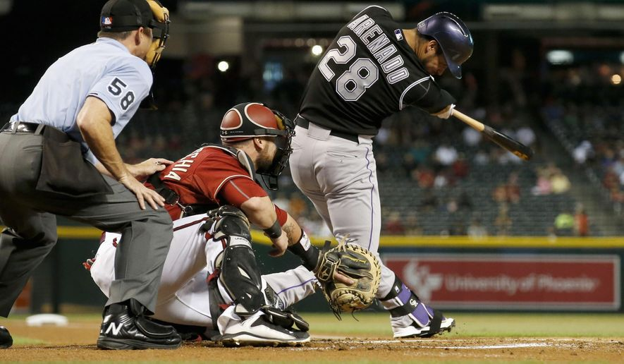 Colorado Rockies' Nolan Arenado (28) hits a fly ball to the outfield as Arizona Diamondbacks' Jarrod Saltalamacchia, middle, and umpire Dan Iassogna (58) watch during the first inning of a baseball game Wednesday, Sept. 30, 2015, in Phoenix. (AP Photo/Ross D. Franklin)