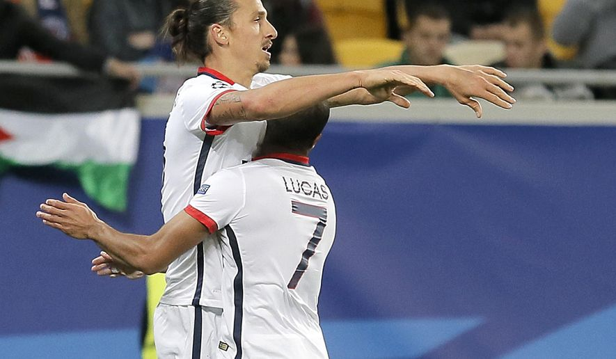 PSG's Zlatan Ibrahimovic, left, celebrates with his teammate Lucas after scoring during the Champions League group A soccer match between Shakhtar Donetsk and Paris Saint Germain at the Arena Lviv stadium in Lviv, Western Ukraine, Wednesday, Sept. 30, 2015. (AP Photo/Efrem Lukatsky)