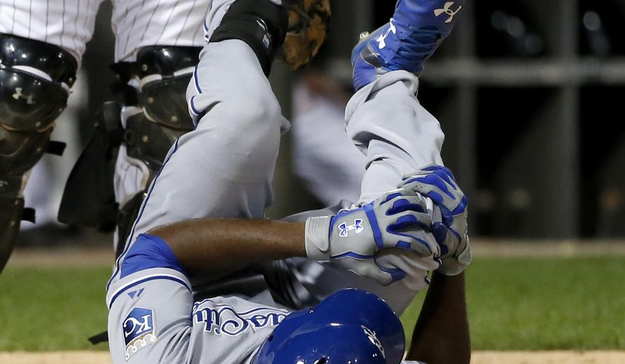 Kansas City Royals' Lorenzo Cain rolls on the ground after fouling a pitch from Chicago White Sox starting pitcher Jose Quintana during the seventh inning of a baseball game Wednesday, Sept. 30, 2015, in Chicago. (AP Photo/Charles Rex Arbogast)