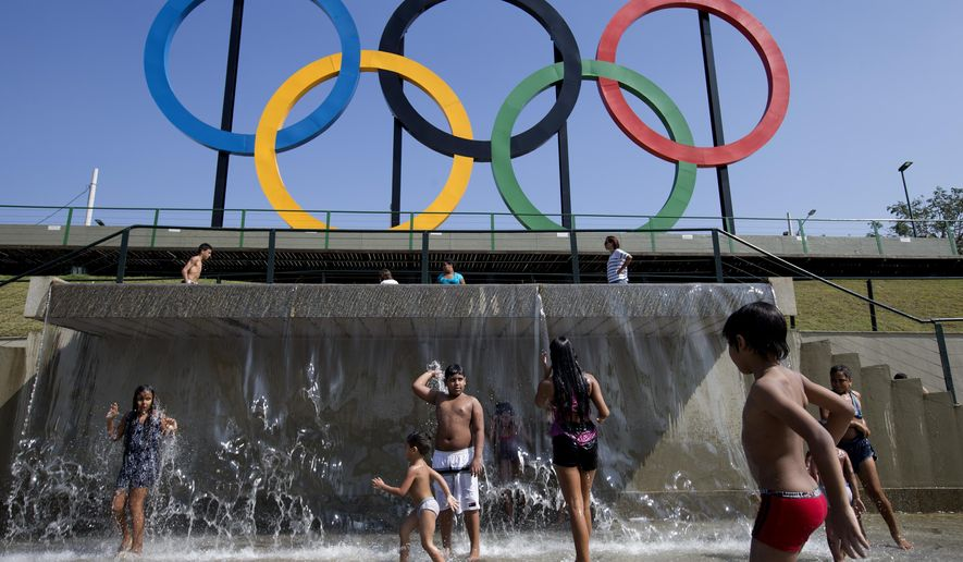FILE - In this July 28, 2015 file photo, children play in a water fountain next to Olympic rings at Madureira Park in Rio de Janeiro, Brazil. Some foreign ticket buyers for next year's Rio Olympics are paying higher prices than they should, failing to benefit from the steep decline in the value of the Brazilian currency against the dollar. (AP Photo/Silvia Izquierdo, File)