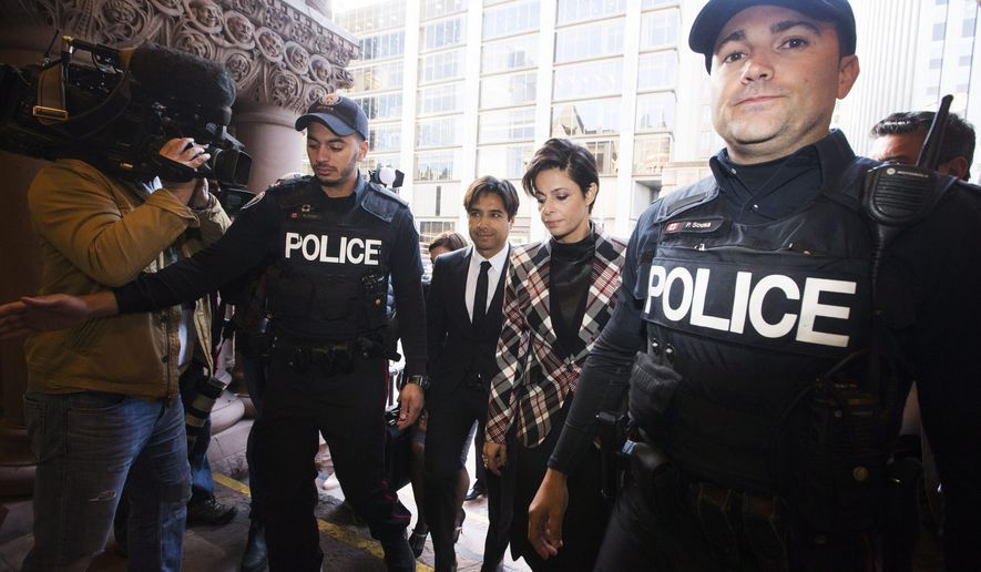 Former CBC radio host Jian Ghomeshi, center, accompanied by his lawyer, Marie Henein, second from right, arrives for a pre-trial hearing for his sexual assault case, in Toronto, on Thursday, Oct. 1, 2015. Ghomeshi has pleaded not guilty to four counts of sexual assault and one count of choking in a case that rocked the country's vaunted public broadcaster. (Michelle Siu/The Canadian Press via AP) MANDATORY CREDIT