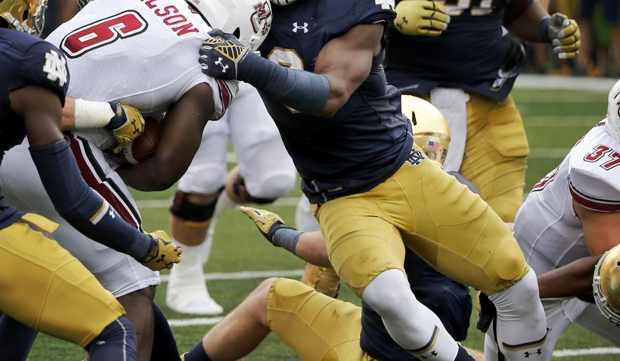 In this Saturday, Sept. 26, 2015 photo, Notre Dame linebacker Jaylon Smith, right, makes a tackle on Massachusetts' Jamal Wilson, during the first half of an NCAA college football game in South Bend, Ind. Jaylon Smith is hard to keep track of. Sometimes he lines up at weakside linebacker spot and rushes the passer. Other times he lines up in the same spot and drops back in coverage. Other times he slides out to play strongside linebacker. Still other times he lines up at defensive end. (AP Photo/Charles Rex Arbogast)