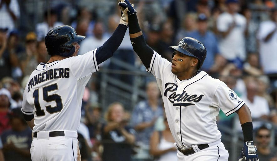San Diego Padres' Yangervis Solarte high fives with Cory Spangenberg after blasting a two run homer against the Milwaukee Brewers in the third inning of a baseball game Thursday, Oct. 1, 2015, in San Diego.  (AP Photo/Lenny Ignelzi)