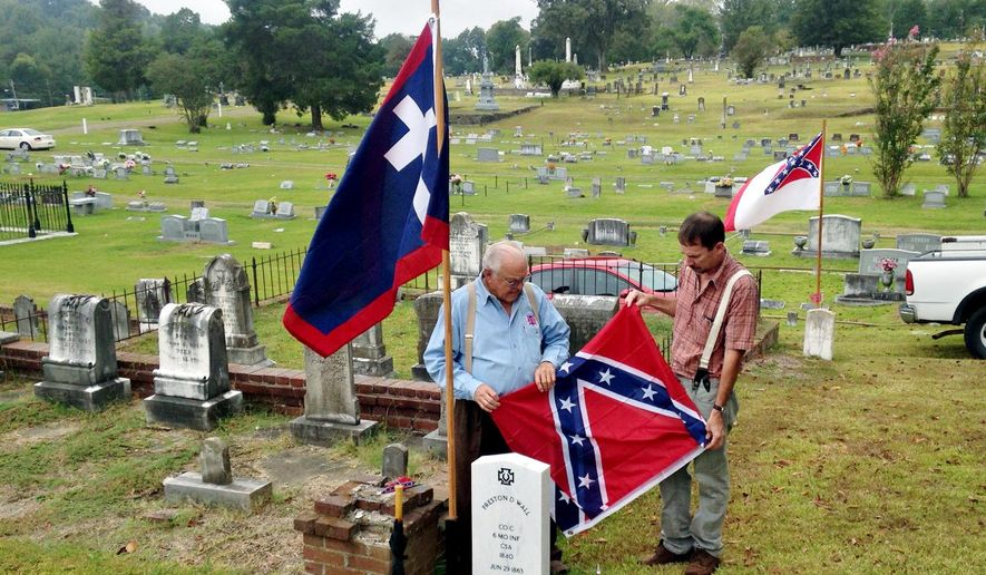 John C. Pemberton Camp of Sons of Confederate Veterans members Wayne McMaster and Bryan Skipworth unveil the tombstone of Pvt. Preston C. Wall, during a funeral ceremony, Tuesday, Sept. 29, 2015 in Vicksburg, Miss.   The   Confederate soldier from Company C of the Missouri Infantry, died June 29, 1863, during the Siege of Vicksburg. (Josh Edwards/The Vicksburg Evening Post via AP) MANDATORY CREDIT