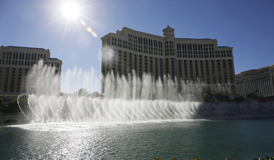 FILE -- In this Aug. 14, 2014 file photo, the sun shines on the fountains of the Bellagio hotel and casino in Las Vegas. Two former craps dealers at the Bellagio and two of their friends have been accused of siphoning more than $1 million off gambling tables over nearly two years by quietly paying phantom bets. (AP Photo/John Locher, File)