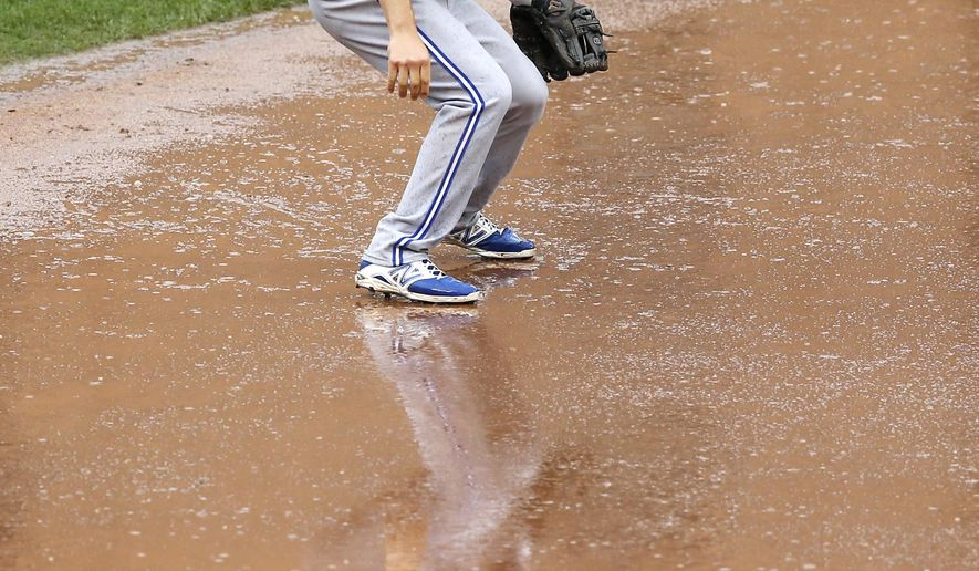 Toronto Blue Jays shortstop Jonathan Diaz is reflected in the infield dirt as rain falls in the first inning of a baseball game against the Baltimore Orioles, Thursday, Oct. 1, 2015, in Baltimore. (AP Photo/Patrick Semansky)