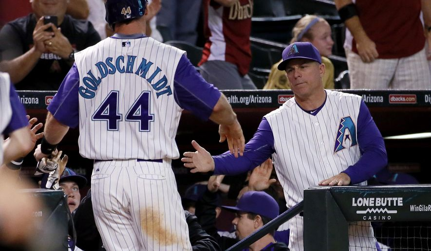 Arizona Diamondbacks' Paul Goldschmidt (44) is greeted by manager Chip Hale after scoring on an RBI double by teammate Welington Castillo during the seventh inning of a baseball game against the Colorado Rockies, Thursday, Oct. 1, 2015, in Phoenix. (AP Photo/Matt York)