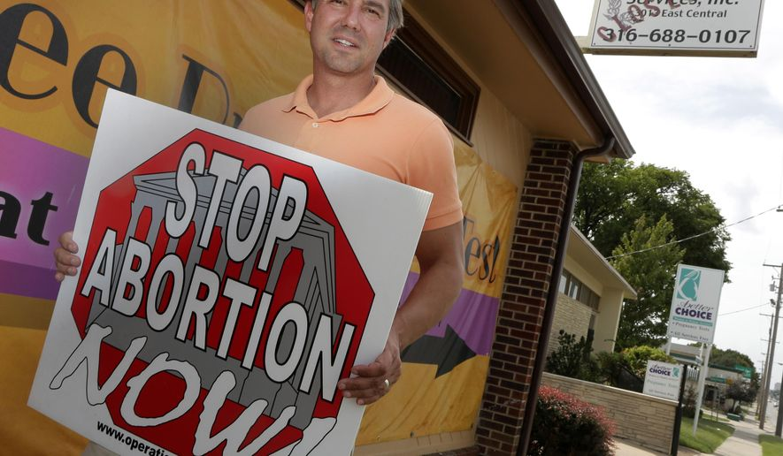 FILE - In this Aug. 23, 2013 file photo, Troy Newman, head of the Kansas-based Operation Rescue, holds an anti-abortion sign outside his headquarters housed in a closed abortion clinic in Wichita, United States. American anti-abortion activist Newman is expected to be deported from Australia amid concerns that he could incite violence. Newman was detained at Melbourne Airport on Thursday, Oct. 1 after trying to enter Australia even though officials had canceled his visa. (AP Photo/Charlie Riedel, File)