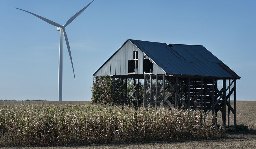 In this photo taken Thursday, Oct. 1, 2015, an old barn is seen next to a wind turbine at the Highland Wind Farm at O'Brien County near Primghar, Iowa/ (Justin Wan/Sioux City Journal via AP) MANDATORY CREDIT