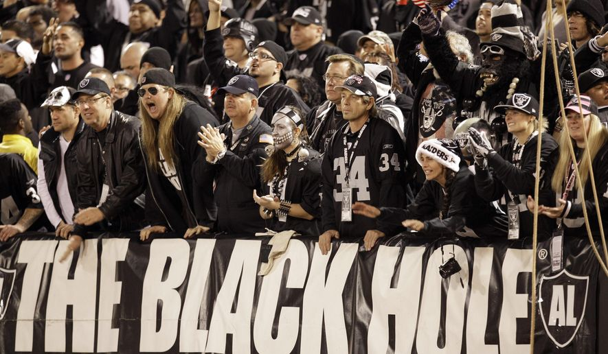FILE - In this Dec. 6, 2012, file photo, The Black Hole fan section is shown during the third quarter of an NFL football game between the Oakland Raiders and the Denver Broncos in Oakland, Calif. The south end zone sections of Oakland-Alameda County Coliseum are known to have some of the rowdiest fans in American sports, face painters who dress up in evil costumes, often with spike-covered shoulder pads. (AP Photo/Ben Margot, File)