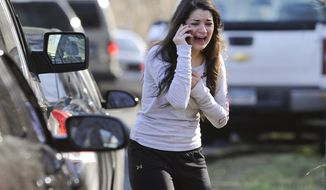In this Dec. 14, 2012 file photo, Carlee Soto uses a phone to ask about her sister, Victoria Soto, a teacher at the Sandy Hook Elementary School in Newtown, Conn., after gunman Adam Lanza killed 26 people inside the school, including 20 children. Victoria Soto, 27, was among those killed. (AP Photo/Jessica Hill, File)
