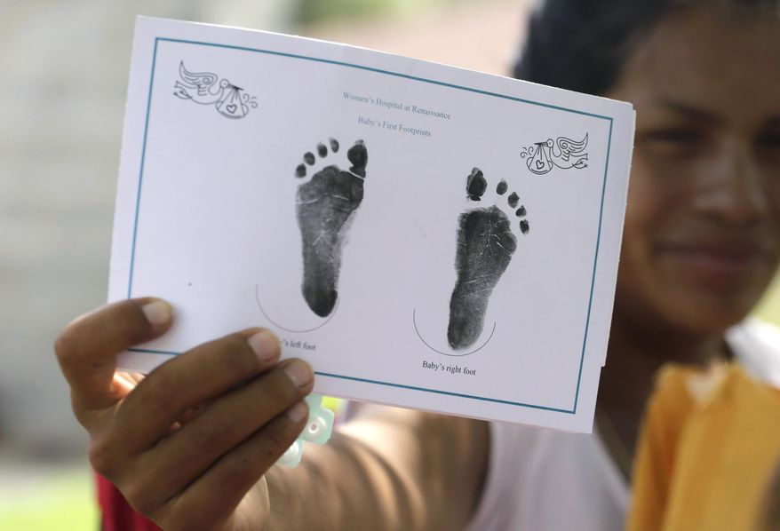 In this Wednesday, Sept. 16, 2015 photo in Sullivan City, Texas, a woman who is in the country illegally shows the footprints of her daughter who was born in the United States but was denied a birth certificate. Lawyers for immigrant families denied birth certificates for their U.S.-born children by Texas health officials who refuse to recognize as valid certain forms of identification will argue for a federal judge to intervene against the state. (AP Photo/Eric Gay)