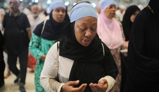 """In this Monday, Sept. 21, 2015 photo, Shahidah Sharif circles the Kaaba, the cubic building at the Grand Mosque in the Muslim holy city of Mecca, Saudi Arabia. As Sharif, an African-American Muslim, joined millions of fellow pilgrims from around the world on the hajj this year, she felt a renewed connection. To her own """"blackness,"""" she says, but also to humanity as a whole. (AP Photo/Mosa'ab Elshamy)"""