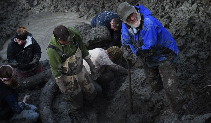 In this photo taken Thursday, Oct. 1, 2015, University of Michigan professor Dan Fisher, right, smiles as he takes a break from leading a team of Michigan students and volunteers as they excavate woolly mammoth bones found on a farm near Chelsea, Mich. (Melanie Maxwell/The Ann Arbor News via AP) LOCAL TELEVISION OUT; LOCAL INTERNET OUT; MANDATORY CREDIT