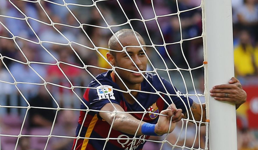 FC Barcelona's Neymar, from Brazil, left, holds the net during a Spanish La Liga soccer match against Las Palmas at the Camp Nou stadium in Barcelona, Spain, Saturday, Sept. 26, 2015. (AP Photo/Manu Fernandez)