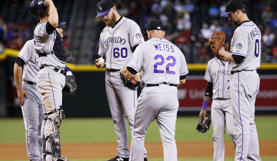 Colorado Rockies relief pitcher Justin Miller (60) is pulled from the game by manger Walt Weiss (22) during the seventh inning of a baseball game against the Arizona Diamondbacks, Thursday, Oct. 1, 2015, in Phoenix. (AP Photo/Matt York)