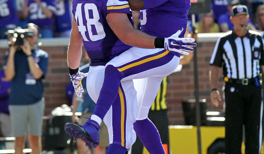 Minnesota Vikings quarterback Teddy Bridgewater (5) jumps into the arms of Zach Line after Line scored a touchdown against the San Diego Chargers in the second half of an NFL football game in Minneapolis, Sunday, Sept. 27, 2015.  (AP Photo/Andy Clayton-King)