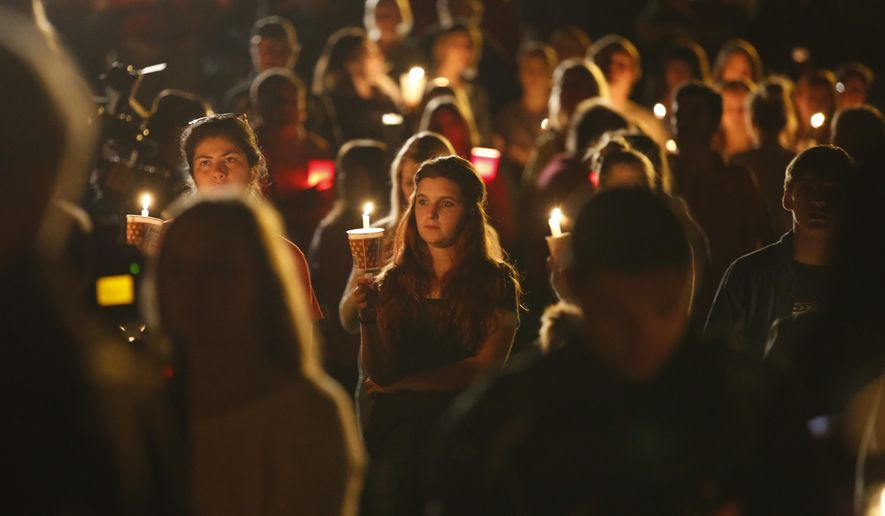 People gather for a candlelight vigil at Stewart Park in Roseburg, Ore., after a shooting with multiple fatalities occurred at Umpqua Community College, Thursday, Oct. 1, 2015. (Randy L. Rasmussen/The Oregonian via AP)