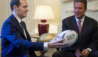 Britain's Chancellor of the Exchequer George Osborne, left,  exchanges a rugby ball for an American football with former American football player Dan Marino, during a media event inside 11 Downing Street in London on Friday Oct. 2, 201  (Justin Tallis/Pool, via AP)