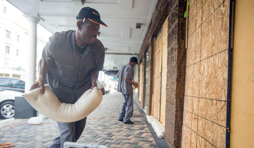 Perry Williams, 47, left, and Alaric Nixon, 28, place sandbags on the storefront of Diamond's International store, in preparation for the arrival of hurricane Joaquin in Nassau, Bahamas, Thursday, Oct. 1, 2015. Joaquin unleashed heavy flooding as it roared through sparsely populated islands in the eastern Bahamas as a Category 4 storm. (AP Photo/Tim Aylen)