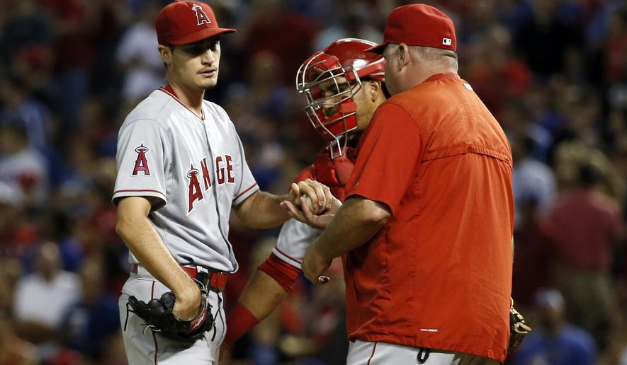Los Angeles Angels starting pitcher Andrew Heaney turns the ball over to manager Mike Scioscia, right, as Carlos Perez, rear, watches in the fifth inning of a baseball game against the Texas Rangers Thursday, Oct. 1, 2015, in Arlington, Texas. (AP Photo/Tony Gutierrez)