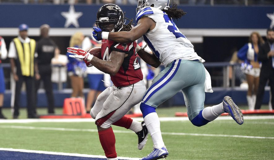 Atlanta Falcons running back Devonta Freeman (24) has his mask held by Dallas Cowboys' J.J. Wilcox (27) as Freeman scored a touchdown during the second half of an NFL football game Sunday, Sept. 27, 2015, in Arlington, Texas. (AP Photo/Michael Ainsworth)