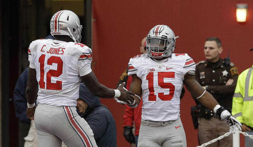Ohio State's Ezekiel Elliott (15) celebrates with Cardale Jones (12) after Elliott ran 55 yards for a touchdown during the second half of an NCAA college football game  against Indiana, Saturday, Oct. 3, 2015 in Bloomington, Ind. (AP Photo/Darron Cummings)