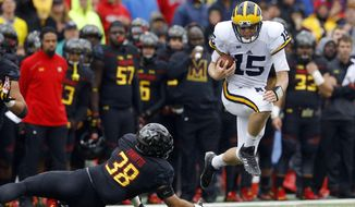 Michigan quarterback Jake Rudock, right, leaps over Maryland linebacker Brett Zanotto in the first half of an NCAA college football game, Saturday, Oct. 3, 2015, in College Park, Md. (AP Photo/Patrick Semansky)