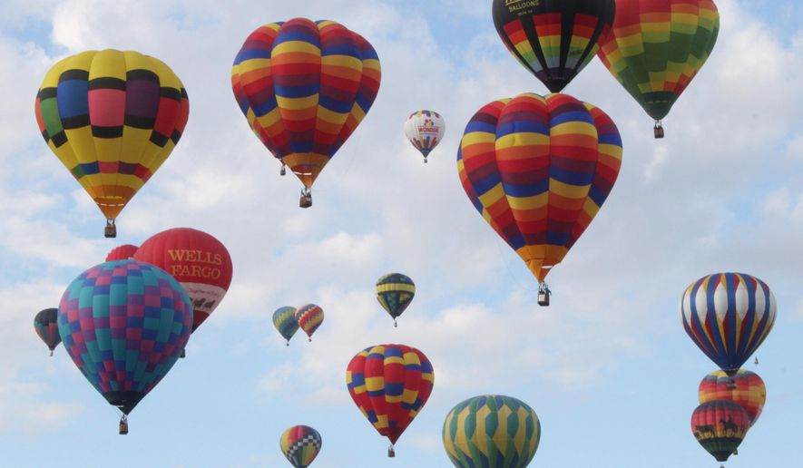 Hundreds of balloons lift off to mark the official start of the annual Albuquerque International Balloon Fiesta during the first mass ascension in Albuquerque, N.M., on Saturday, Oct. 3, 2015. The nine-day event attracts hundreds of balloonists and thousands of spectators from around the world. (AP Photo/Susan Montoya Bryan)