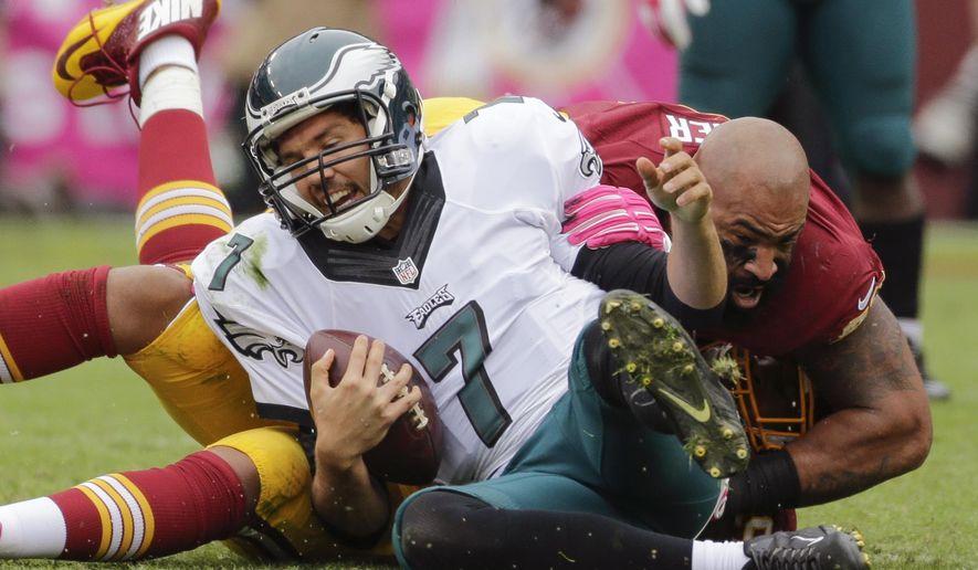 Washington Redskins defensive end Jason Hatcher (97) looses his helmut during a sack of Philadelphia Eagles quarterback Sam Bradford (7) during the first half of an NFL football game in Landover, Md., Sunday, Oct. 4, 2015. (AP Photo/Mark Tenally)