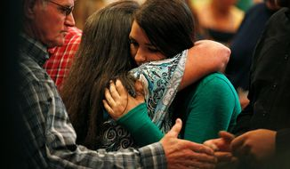 Lacey Scroggins, a survivor of the shooting at Umpqua Community College (right), embraces another woman during a church service Sunday in Roseburg, Oregon. Despite President Obama's impassioned speech, no change on gun policy is expected. (Associated Press photographs)