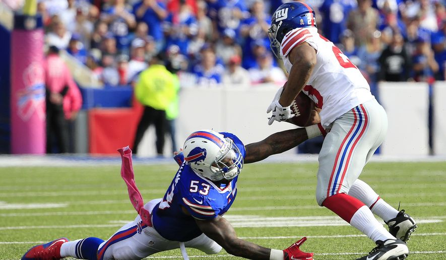 New York Giants running back Rashad Jennings, right, breaks a tackle attempt by Buffalo Bills outside linebacker Nigel Bradham on his way to score a touchdown run during the second half of an NFL football game, Sunday, Oct. 4, 2015, in Orchard Park, N.Y. (AP Photo/Bill Wippert)